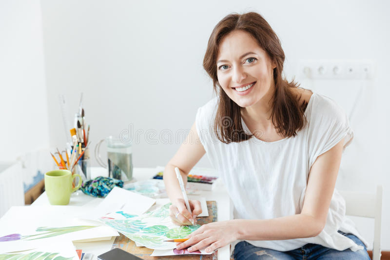 Cheerful woman artist sitting and drawing in art studio stock photo
