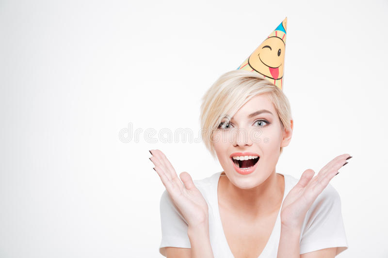 Cheerful woman in birthday hat looking at camera. Isolated on a white background stock photo