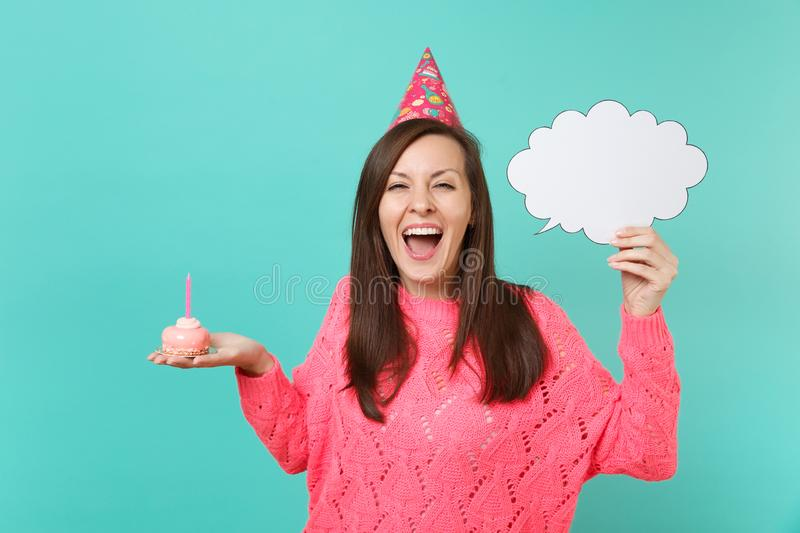 Cheerful woman in birthday hat screaming, hold cake with candle, empty blank Say cloud, speech bubble for promotional. Content isolated on blue background stock images