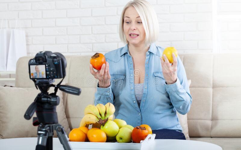 Happy woman blogger shows fruits to the camera at home royalty free stock photography