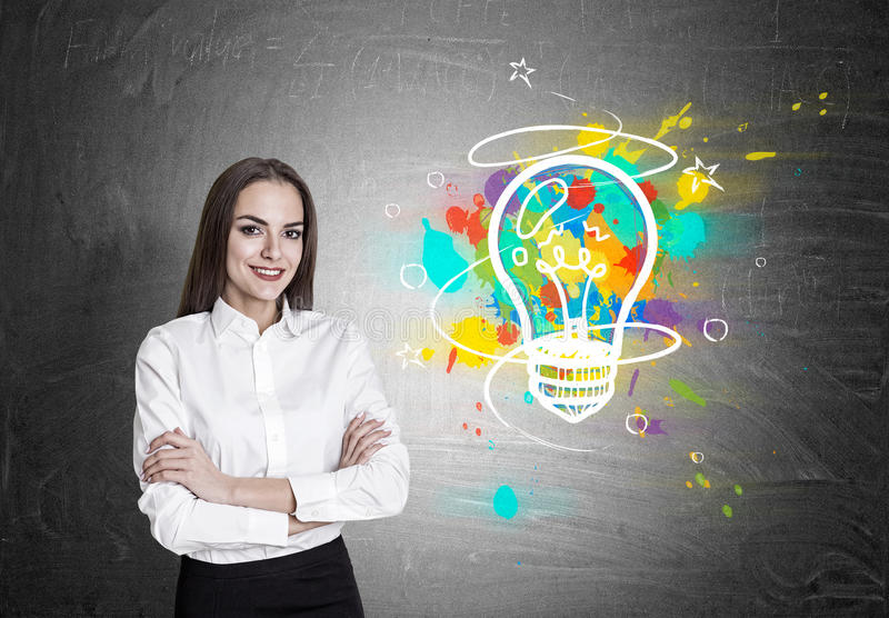 Cheerful woman and bright light on blackboard. Portrait of a cheerful businesswoman standing near a blackboard with her arms crossed. There is a colorful light royalty free stock photo