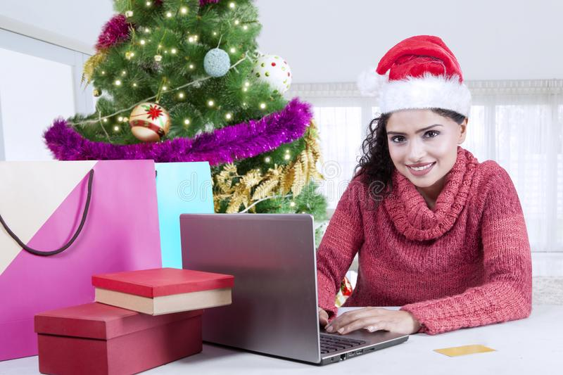 Cheerful woman buying Christmas gifts online stock images