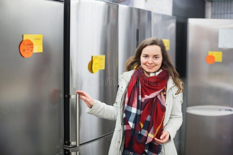 Cheerful woman buying domestic refrigerator. Cheerful young woman buying domestic refrigerator in supermarket stock photo