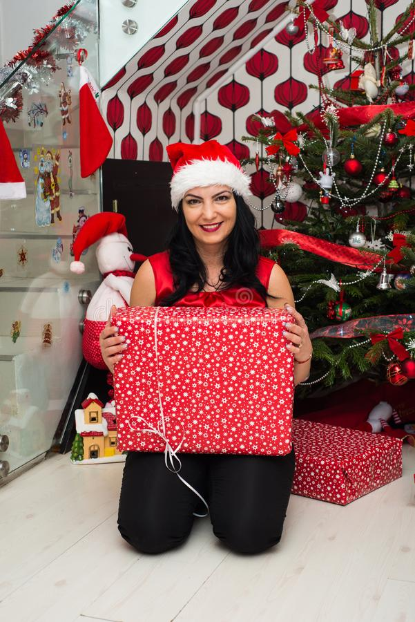 Cheerful woman with Christmas gift. In front of tree in her home royalty free stock photography