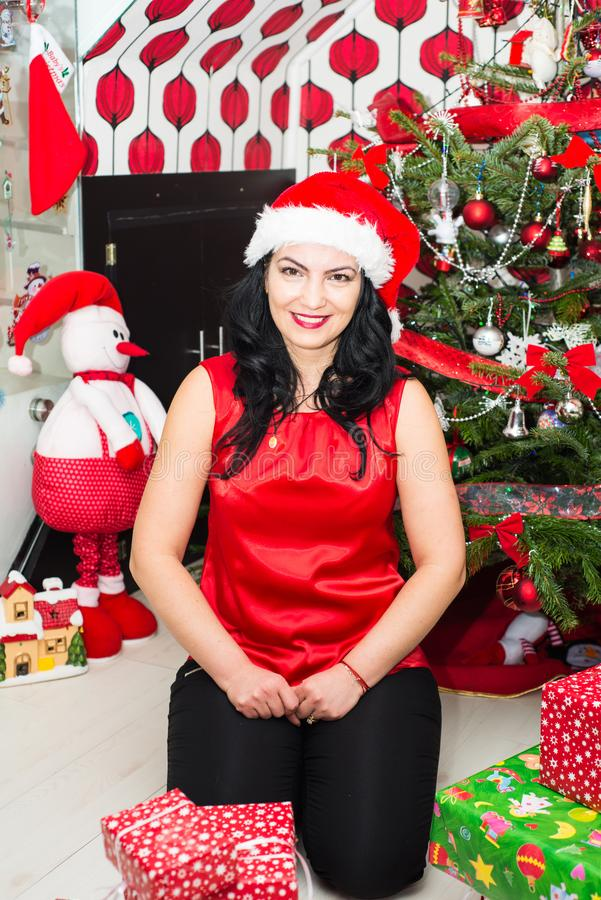 Cheerful woman at Christmas tree. Cheerful woman with Christmas tree wrapping presents royalty free stock image