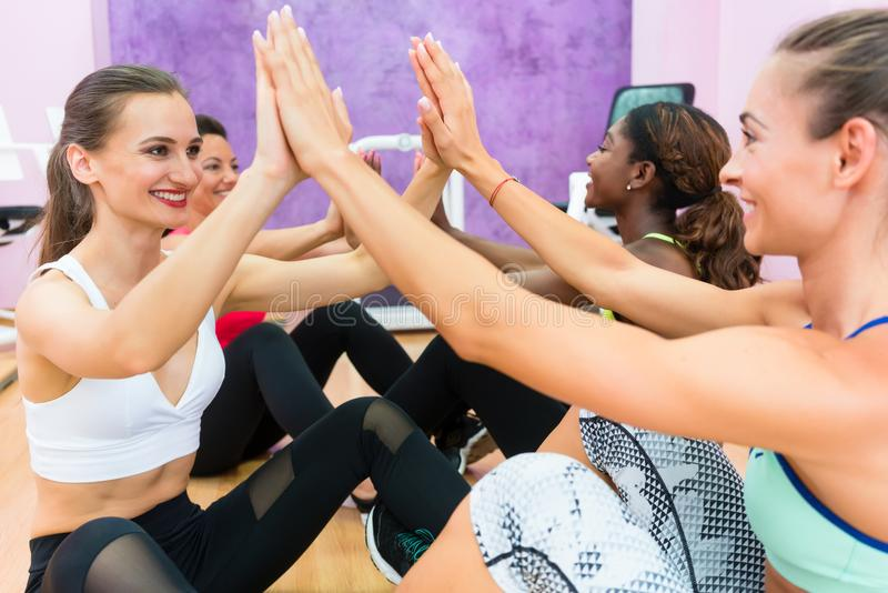 Cheerful woman clapping the hands in workout during group class royalty free stock photography