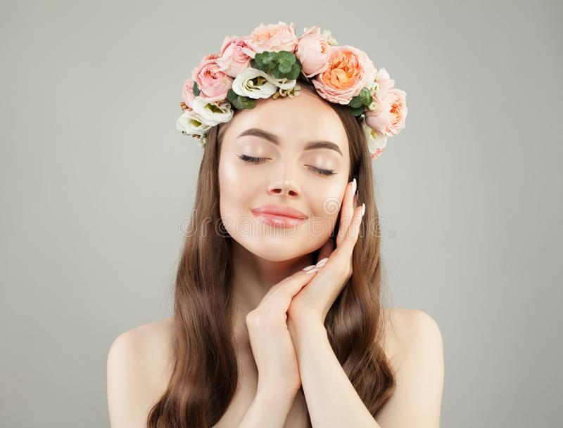 Cheerful woman with clear skin and flowers. Skincare and facial treatment.  royalty free stock image