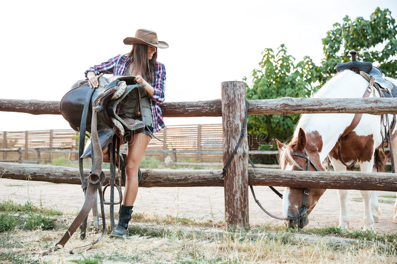 Cheerful woman cowgirl in hat holding saddle for riding horse royalty free stock photo