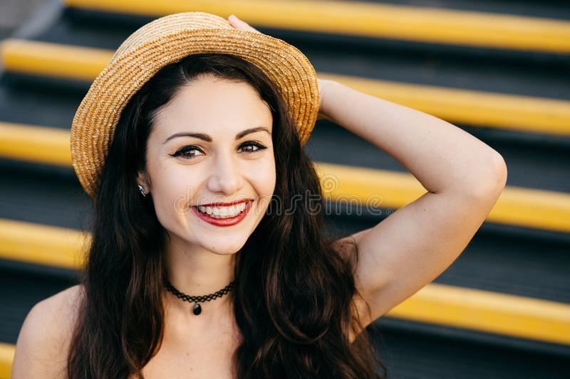 Cheerful woman with dark hair, healthy skin, bright eyes wearing straw hat on head sitting at stairs keeping her hand on head smil royalty free stock image