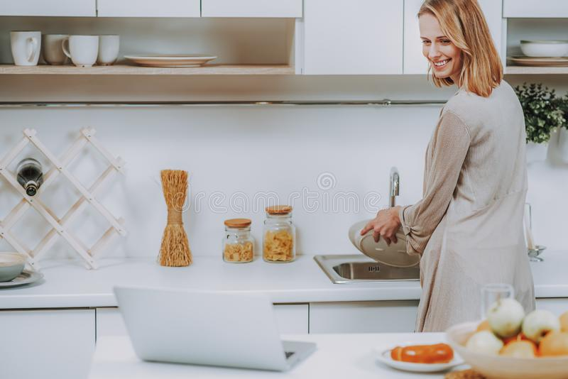 Cheerful woman is doing washing-up in kitchen stock photo