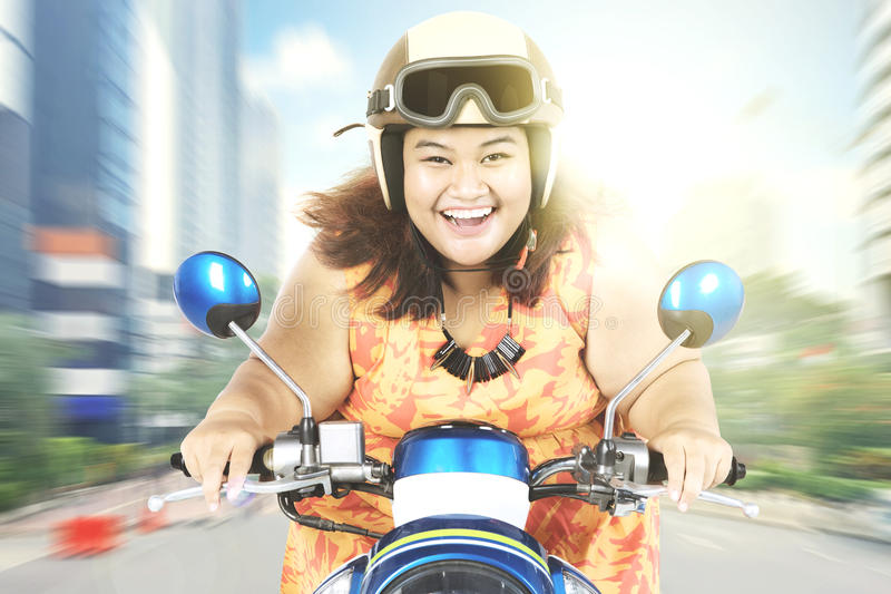 Cheerful woman driving a motorcycle royalty free stock photo