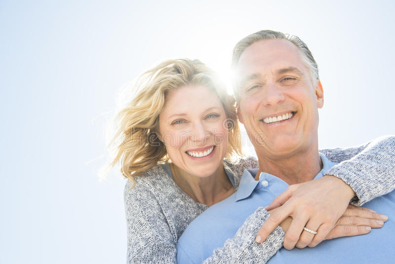Cheerful Woman Embracing Man From Behind Against Sky royalty free stock image