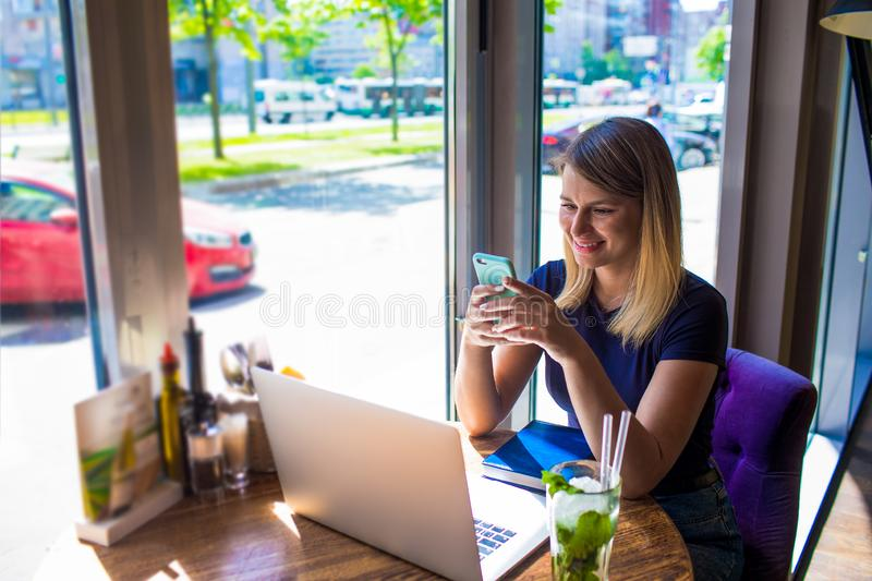 Cheerful woman experienced business writer for executive summary reading e-mail on mobile phone after work on laptop computer stock photo