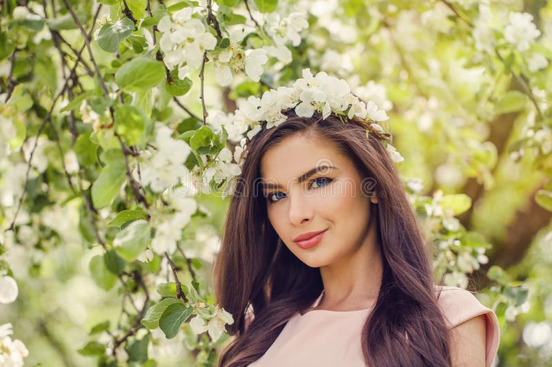 Cheerful woman face in spring flowers outdoors. stock photos