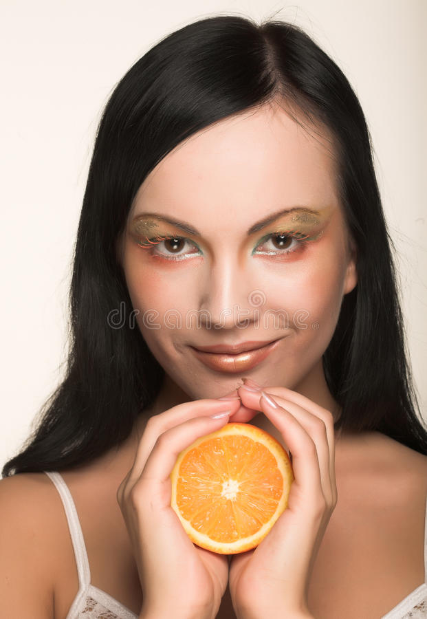 Cheerful woman with fresh orange near her face. Beautiful cheerful woman with fresh orange near her face royalty free stock photo