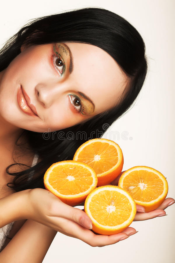 Cheerful woman with fresh orange near her face. Beautiful cheerful woman with fresh orange near her face royalty free stock photography