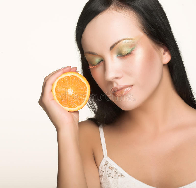 Cheerful woman with fresh orange near her face. Beautiful cheerful woman with fresh orange near her face stock photos
