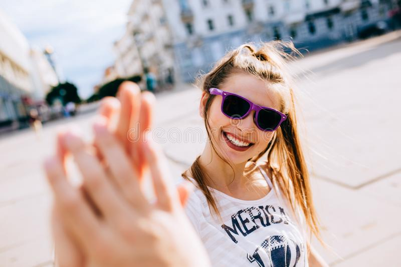 Cheerful woman giving high five to friend while strolling in the city royalty free stock photography