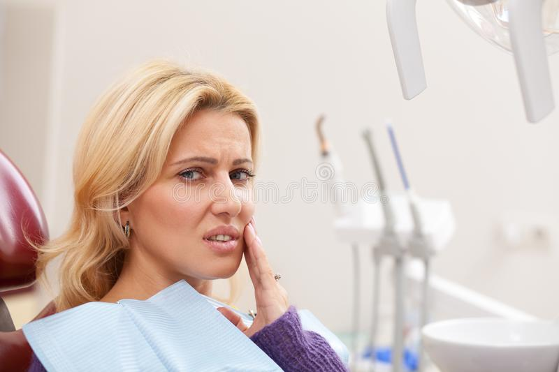 Cheerful woman having dental checkup. Close up of a beautiful mature woman looking exhausted suffering from toothache, copy space. Female patient with painful stock image