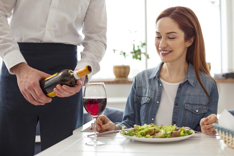 Cheerful woman having dinner in a restaurant stock images