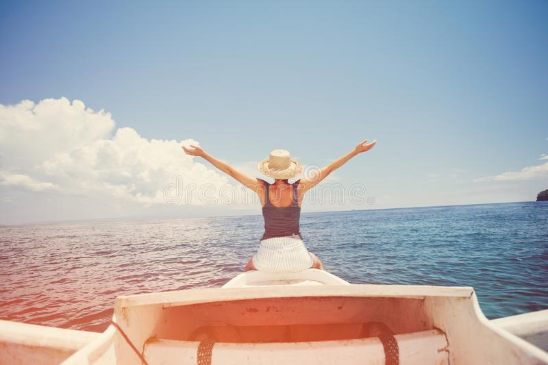 Cheerful woman having fun on the boat floating in the ocean. Intentional sun glare royalty free stock photos