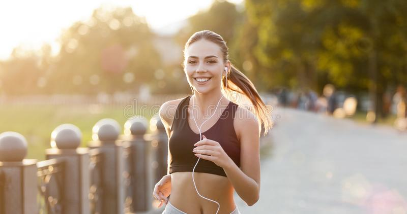 Cheerful woman with headphones running in park. Listening to music during workout, panorama royalty free stock photography