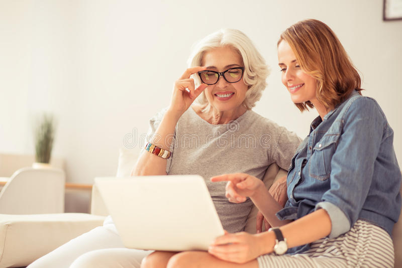 Cheerful woman and her daughter using laptop stock images