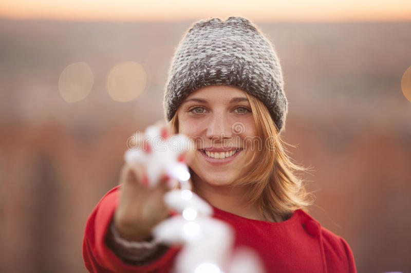 Cheerful woman holding a christmas star with magic illumination. In the park at sunset royalty free stock photo