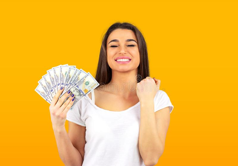 Cheerful woman holding money and celebrating success stock photo