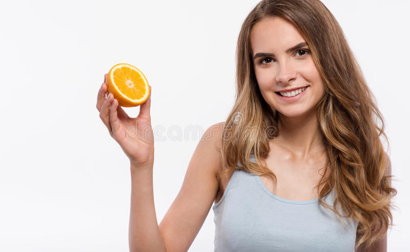 Cheerful woman holding orange stock photography