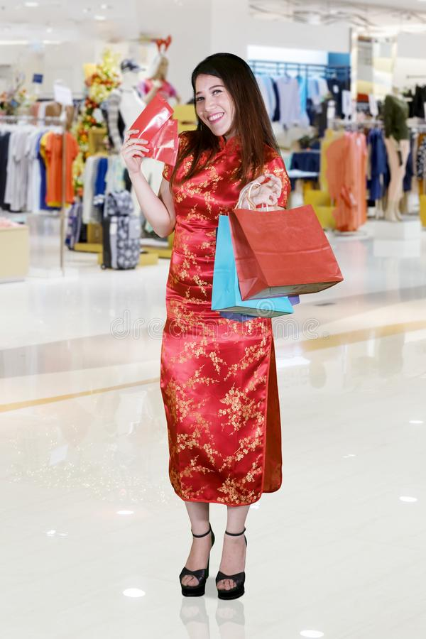 Cheerful woman holds envelope in the mall stock image