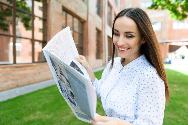Cheerful woman is interested in news stock image