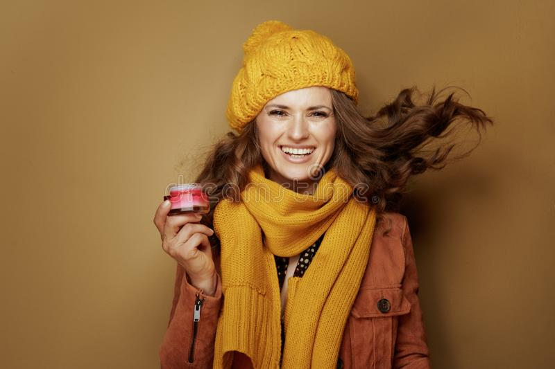 Cheerful woman with jar of facial creme on bronze background. Hello autumn. Portrait of cheerful elegant woman in yellow beret and scarf with jar of facial creme stock image