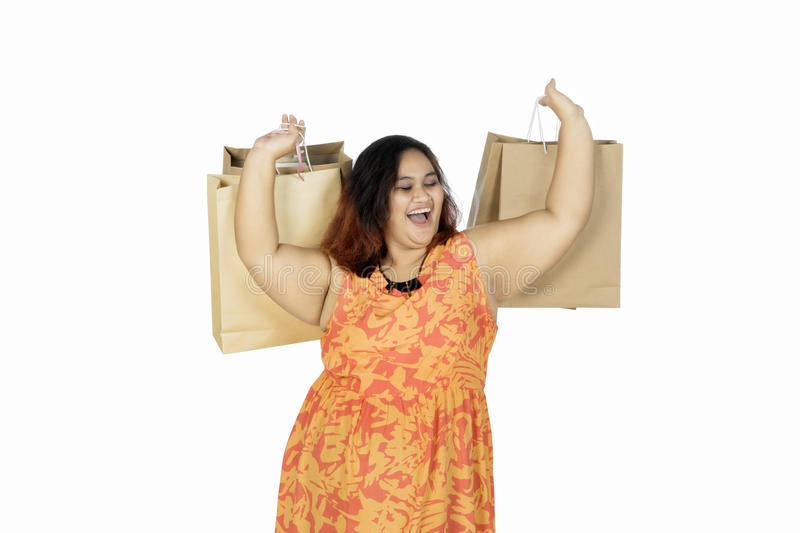 Cheerful woman lifting shopping bags royalty free stock photo