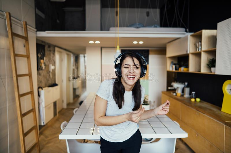 Cheerful woman listening to music with large headphones and singing.Music therapy,mood beneficial practice.Mental health. Improvement,relaxation and stress royalty free stock image