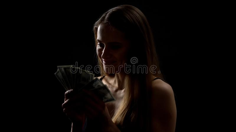 Cheerful woman looking at bunch of dollar banknotes, easy money, casino winner royalty free stock image