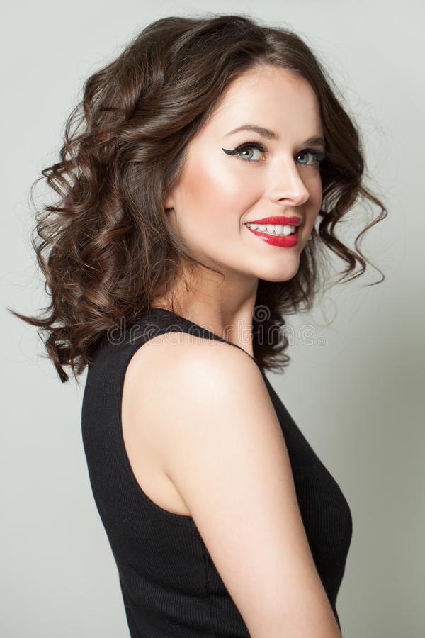 Cheerful woman with makeup and curly hair. Pretty model smiling royalty free stock images