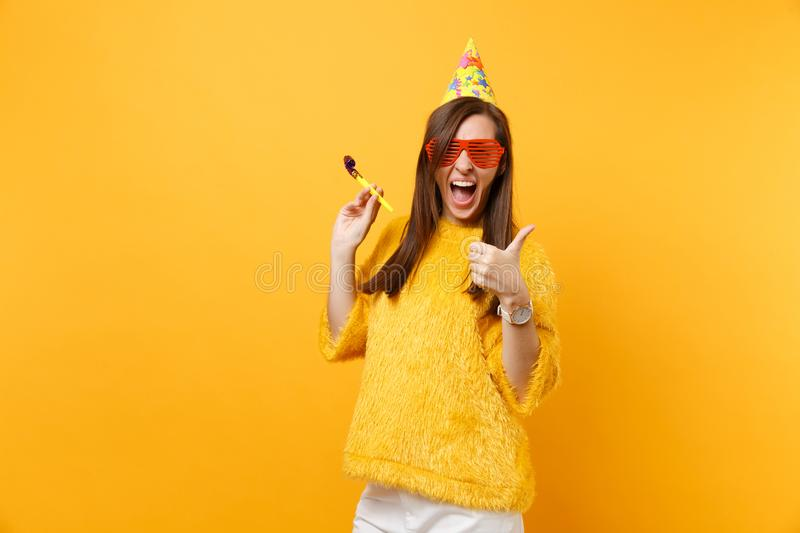 Cheerful woman in orange funny glasses, birthday hat with playing pipe showing thumb up, celebrating isolated on bright. Yellow background. People sincere royalty free stock photography