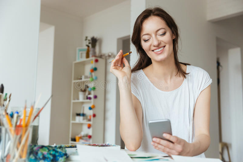 Cheerful woman painter using cell phone in art studio stock images