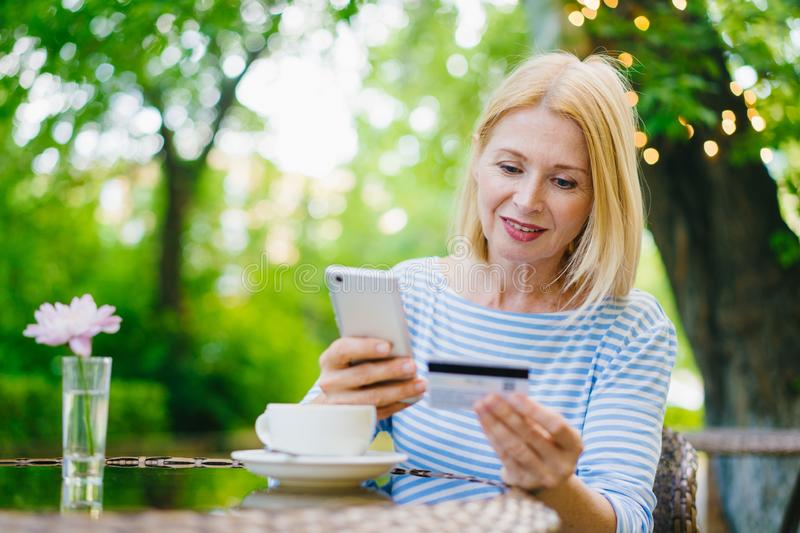 Cheerful woman paying with credit card online in internet shop in outdoor cafe. Cheerful woman is paying with credit card online in internet shop entering bank royalty free stock photo