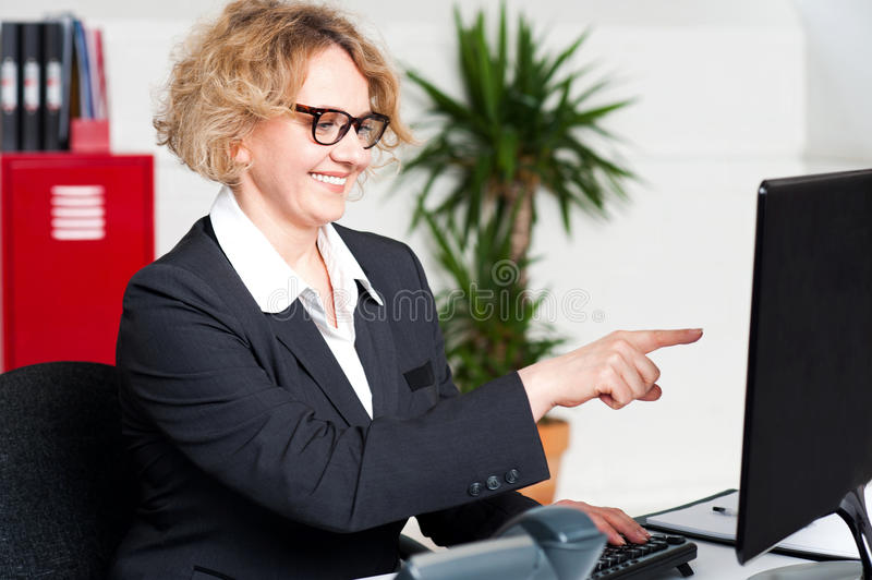 Cheerful Woman Pointing At Computer Screen Stock Image