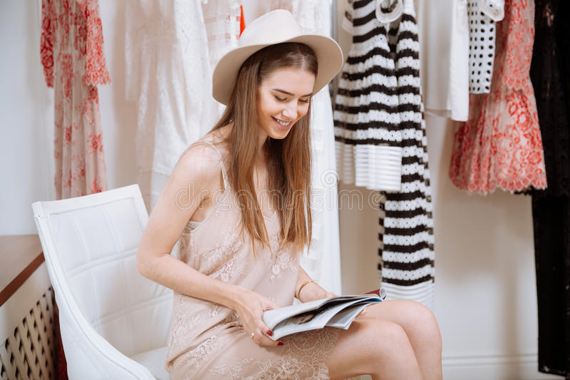 Cheerful woman reading magazine in clothes shop royalty free stock photography