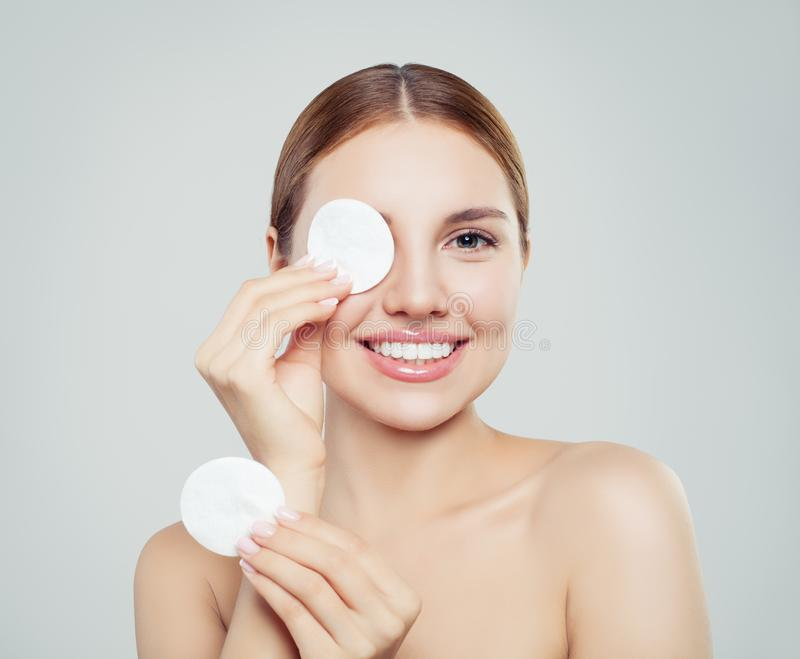 Cheerful woman removing face makeup with a cotton pad. On white background stock photo