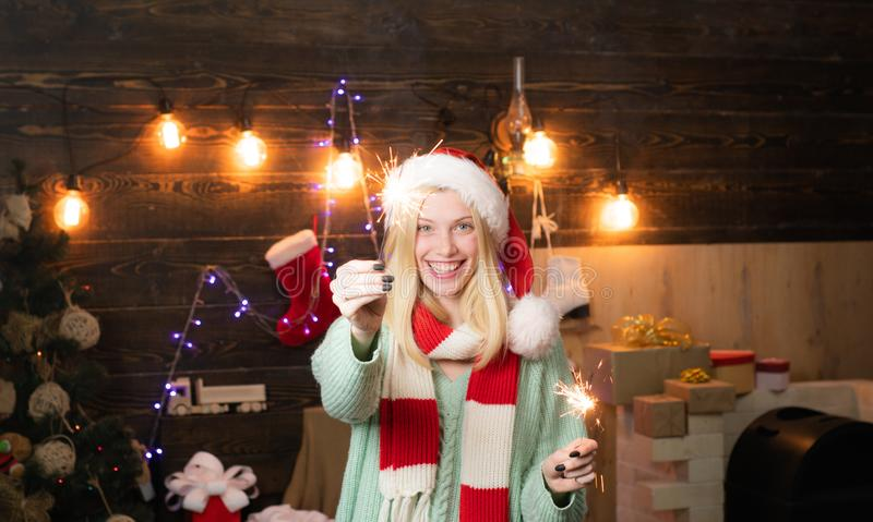 Cheerful woman in santa claus hat. christmas shopping. xmas present box. new year tree decoration. party fire garland stock photography