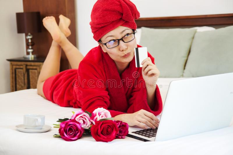 Cheerful woman shopping online with credit card and laptop computer on a bed. royalty free stock photography