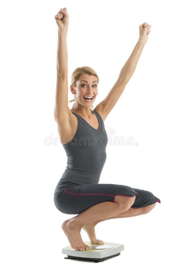 Cheerful Woman Shouting While Crouching On Weight Scale Royalty Free Stock Photography