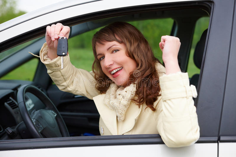 Cheerful woman showing car keys royalty free stock photography