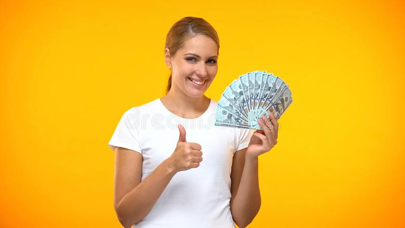 Cheerful woman showing thumbs up holding dollars in hand, well paid job, profit royalty free stock photos