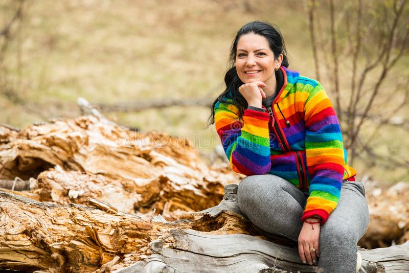 Cheerful woman in nature. Cheerful woman sitting on a bark tree in nature and holding hand to chin royalty free stock photo