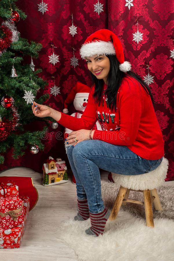 Cheerful Christmas woman. Cheerful woman sitting on fur chair near Christmas tree in her house stock photography